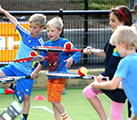 Children playing balance the ball on the tennis racket