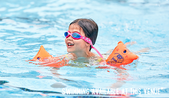 Child swimming with armbands and goggles